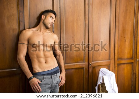 Sexy handsome young man standing shirtless in his bedroom with a shirt draped over chair with a smile - stock photo