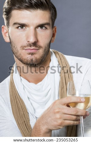 Sexy handsome young man with a beard wearing an elegant scarf drinking white wine and looking at the camera with a serious intense expression - stock photo