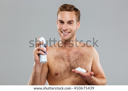 Sexy handsome young man with a shaving foam isolated on the gray background