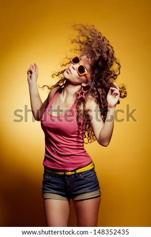 Sexy happy woman dancing excited on yellow background - stock photo