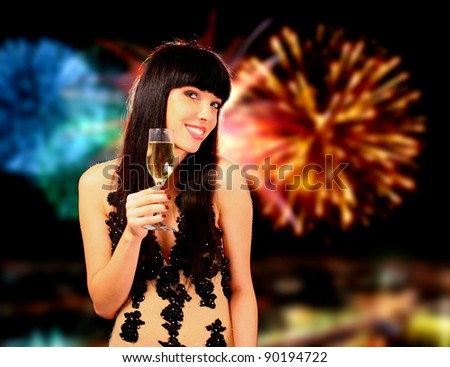Sexy happy woman with champagne over fireworks background - stock photo