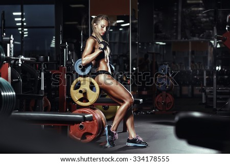 Sexy hot blonde fitness bikini girl with perfect shape body posing and relaxing in gym - stock photo