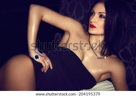 Sexy hot stylish brunette girl model lying in black lingerie witgh bright makeup and red lips - stock photo