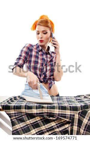 Sexy housewife talking to the phone while ironing, isolated over white background - stock photo