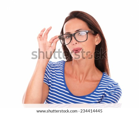 Sexy lady holding spectacles while smiling and looking at camera in white background