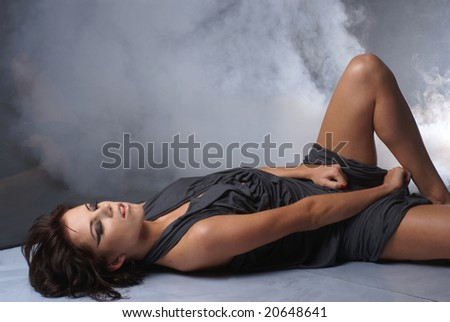 Sexy lady in a silk dress over smoky background