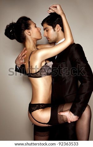Sexy lady in black lingerie and businessman in suit in passionate embrace - stock photo