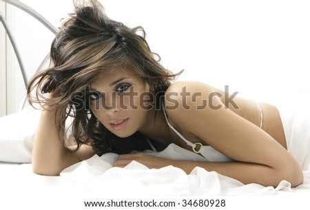 Sexy lady on big white bed - stock photo