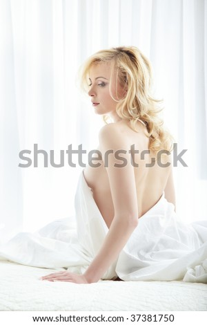 Sexy lady with naked back relaxing on the bed