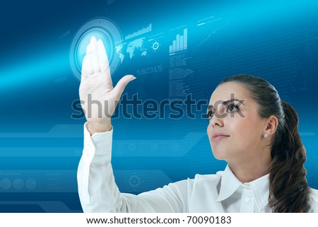 Sexy latina brunette touching button in the future. Looking at the transparent screen with interface. Pretty young business people in interiors / interfaces series. - stock photo