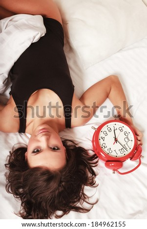 Sexy lazy girl in black body lying with red alarm clock on the bed. Young attractive woman relaxing lazing in her bedroom at the morning. - stock photo