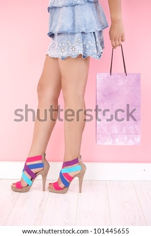 Sexy legs in mini skirt and multicolour sandals.