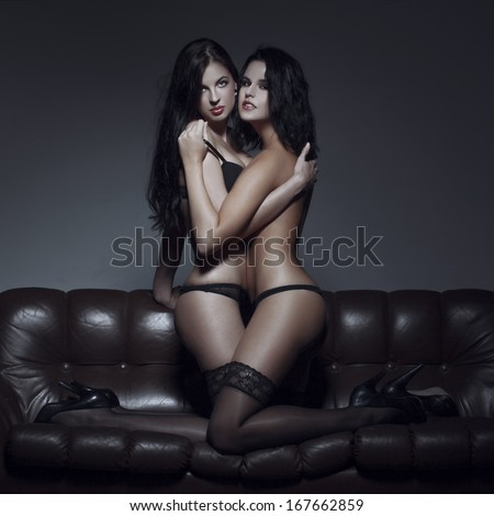 Sexy lesbian couple foreplay on sofa at night, kneeling - stock photo