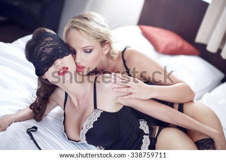 Sexy lesbian lovers foreplay in bed at morning - stock photo