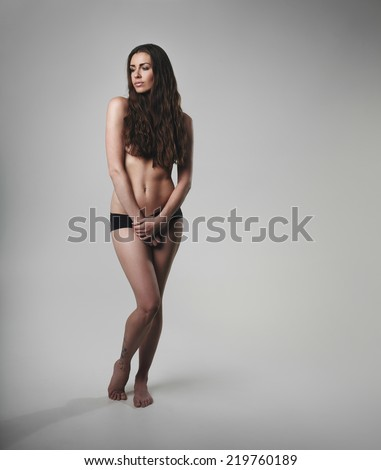 Sexy long hair brunette woman wearing panties. Shirtless female model posing on grey background - stock photo