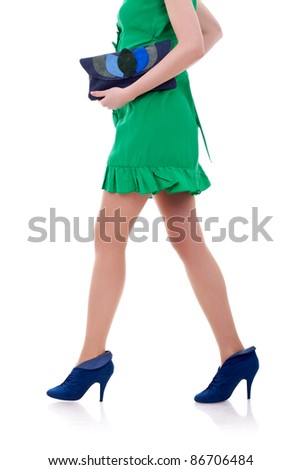 Sexy long legs of fashion model in short dress walking with a purse in her hands - stock photo