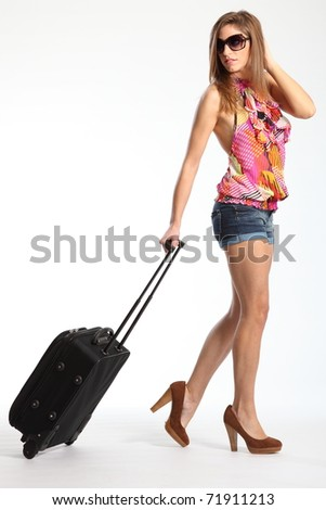 Sexy long legs of woman going on holiday with suitcase - stock photo