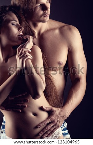 Sexy love couple on dark background - stock photo