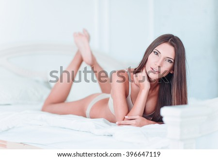 Sexy lovely young girl in lingerie lying on a bed - stock photo