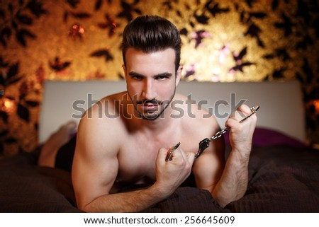 Sexy macho man laying with handcuffs in hotel room - stock photo