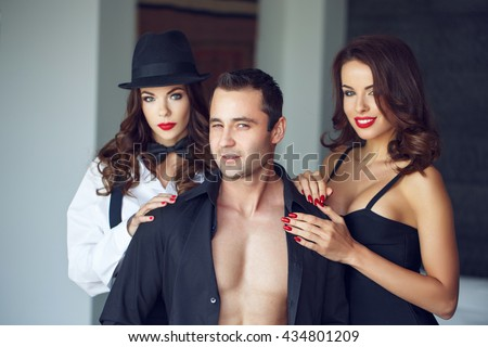 Sexy macho man winking with wife and lover in luxury flat, bigamy - stock photo