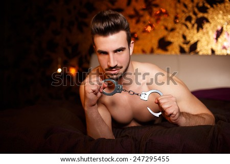 Sexy macho man with handcuffs laying on bed, bdsm - stock photo