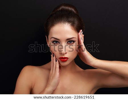 Sexy makeup female model posing with hand near face on black background