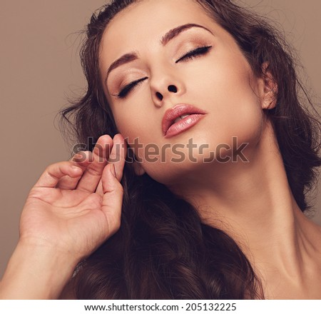 Sexy makeup woman with close eyes and brown long hair. Closeup vintage art portrait
