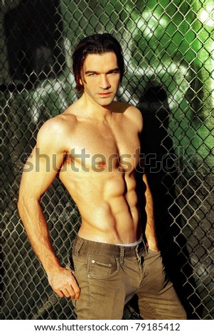 Sexy male fashion model shirtless against graffiti and fence - stock photo