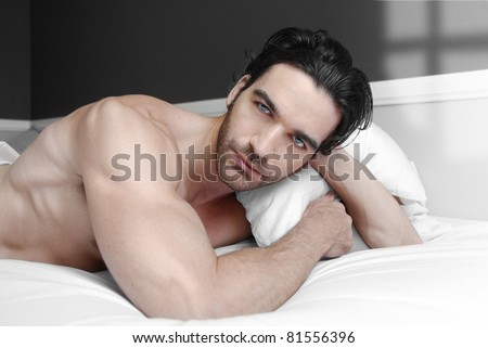 Sexy male model alone in bed