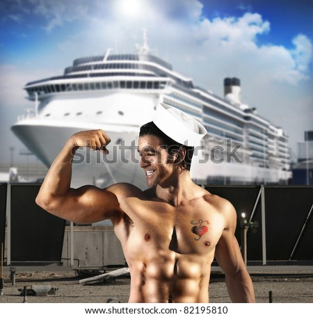 Sexy male model as sailor flexing his bicep in front of ship at port with a heart tattoo on his chest - stock photo
