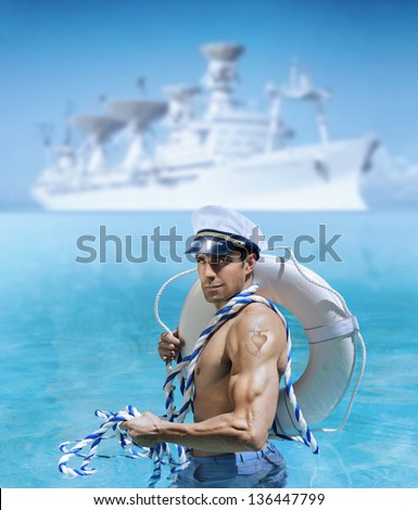Sexy male model as sailor flexing his bicep in front of ship at port with a heart tattoo on his arm - stock photo