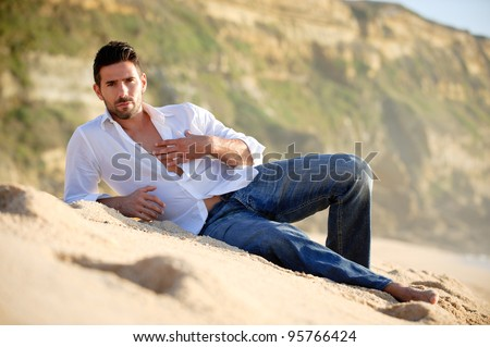 sexy male model on the sand at the beach at sunset - stock photo