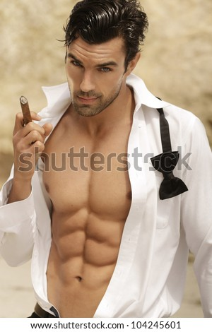 Sexy male model smoking cigar in open formal attire exposing great toned muscular body and abs - stock photo