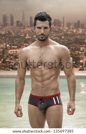 Sexy male model with great body and abs at pool with city in background