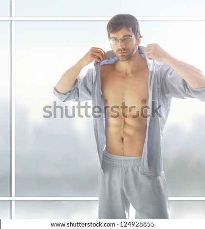 Sexy male model with hot naked body with open shirt against modern background window - stock photo