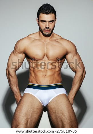 Sexy male muscular model in white underwear on white background with shadow - stock photo