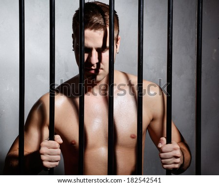 Sexy man behind iron prison bars