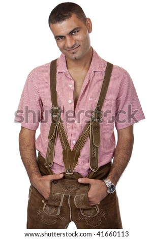 Sexy man dressed in Oktoberfest leather trousers (lederhose) is standing casual and looks happy into camera. Isolated on white. - stock photo