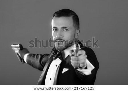 Sexy man gangster agent criminal police in a tuxedo pointing two guns black and white portrait - stock photo