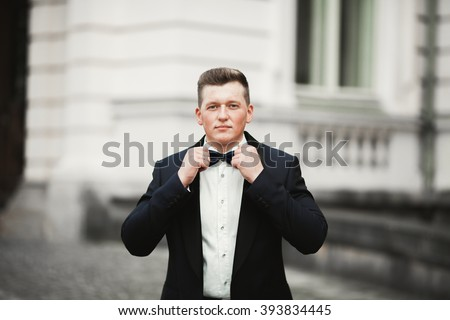 Sexy man, groom posing in old city - stock photo