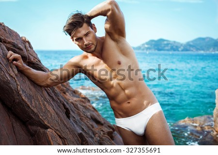 Sexy man in underwear posing on sea scenery - stock photo