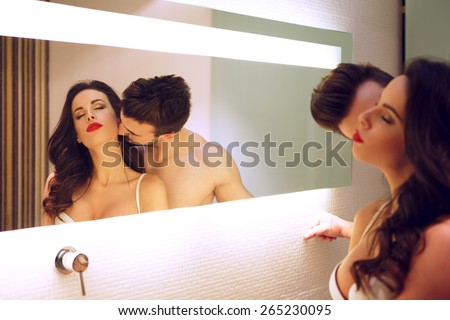 Sexy man kissing woman neck at mirror in bathroom, passionate couple - stock photo
