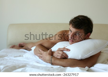 Sexy man lying on a bed - stock photo