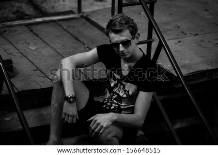 Sexy man posing on rooftop near railing