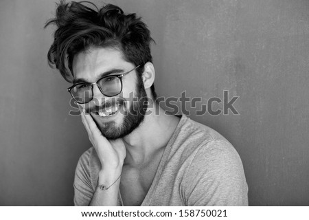 sexy man with beard smiling big against wall - stock photo