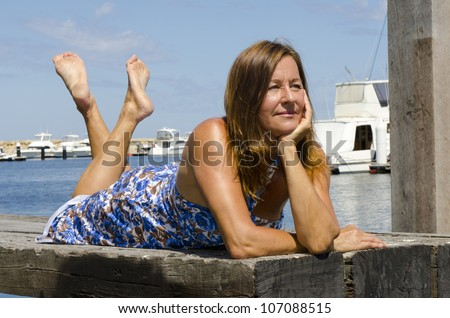 Sexy mature woman enjoying a relaxed sunny day out at a marina, with boats as background, isolated with blue sky as copy space. - stock photo