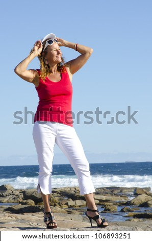 Sexy middle aged woman standing at the ocean wearing red top, white pants and high heel shoes, isolated with happy relaxed smile and sea and blue sky as background and copy space. - stock photo