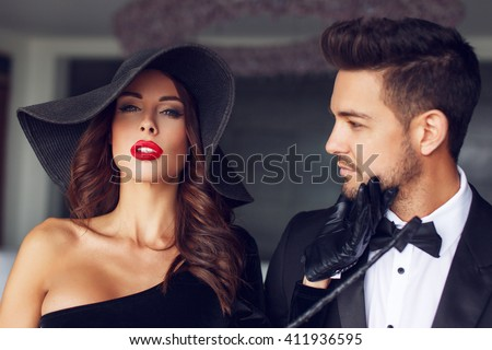Sexy milf woman in hat with young lover in tuxedo in luxury flat - stock photo