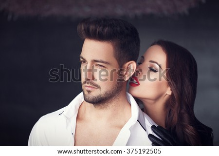 Sexy milf woman whispering macho man indoor - stock photo